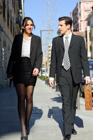 businesswoman suit: Retrato de una gente de negocios atractivos caminando por la calle Pareja trabajo Foto de archivo