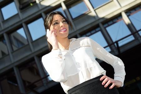 secretaries: Retrato de una mujer de negocios hermosa sonriente en el tel�fono en un edificio de oficinas