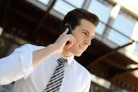 Portrait of an attractive businessman making a call using a smart phone in an office building photo