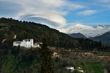 lenticular: Aerial view of Alhambra and snowing Sierra Nevada mountains under a lenticular cloud