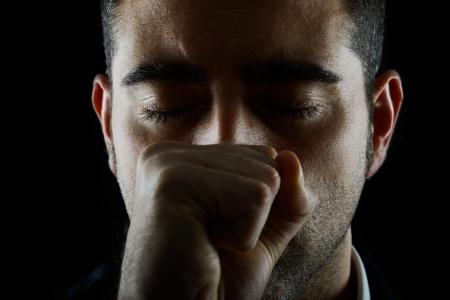 ojos tristes: Retrato de un hombre con el puño y los ojos cerrados sobre fondo negro