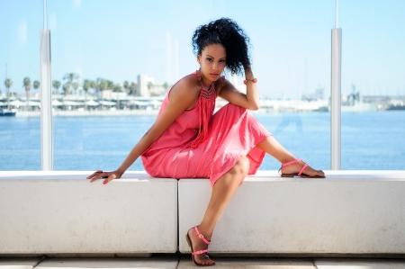 cabello negro: Retrato de una mujer joven negro, modelo de la moda, con un vestido rosa y aretes peinado afro