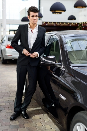 Portrait of a young handsome man, model of fashion, wearing suit and with luxury car  photo