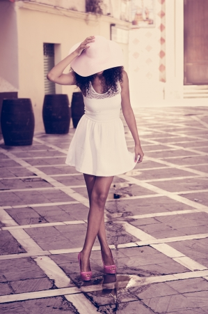 sun hat: Portrait of a young black woman, model of fashion wearing dress and sun hat, with afro hairstyle in urban background