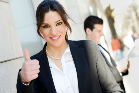 Portrait of an attractive businesswoman showing thumb up sign  Couple working   photo