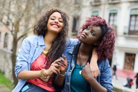 black girl: Portrait von zwei hübschen Mädchen in städtischen backgrund, schwarzen und gemischten Frauen Freunde reden