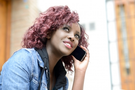 Portrait of beautiful black woman in urban background on the phone photo