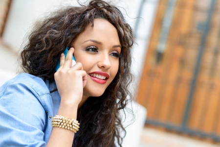 Portrait of beautiful mixed woman in urban background on the phone photo