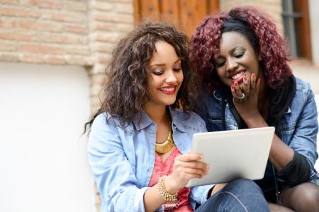 black girl: Portrait von zwei schöne Mädchen mit Tablet-Computer in den städtischen backgrund, schwarzen und gemischten Frauen Freunde reden