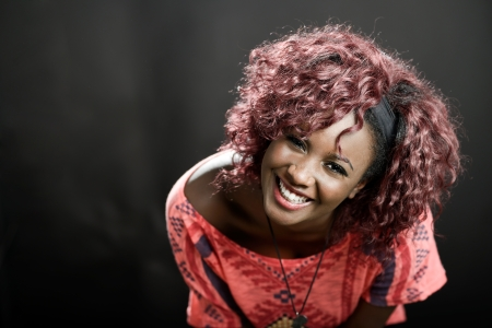 Portrait of beautiful black woman on black background with red hair  Afro hairstyle  Studio shot