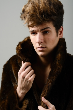 Portrait of a attractive young man wearing fur coat with modern hairstyle photo