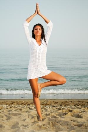 Pretty woman doing yoga on the beach  Stock Photo - 19147774