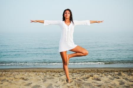 salud sexual: Mujer bonita que hace yoga en la playa