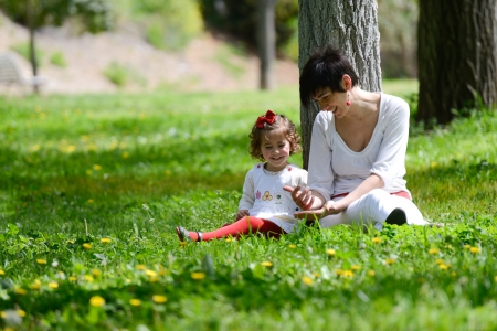 Portrait of mother and little girl playing in the park photo