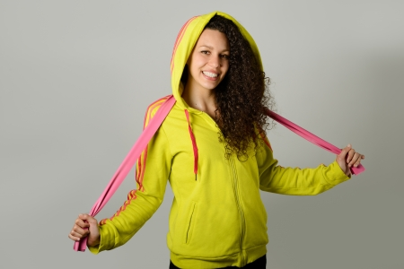 sports wear: Portrait of young cheerful smiling woman in sports wear on urban background