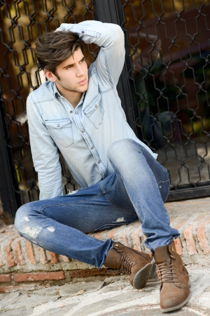 denim jeans: Portrait of a young handsome man, model of fashion, with modern hairstyle in urban background