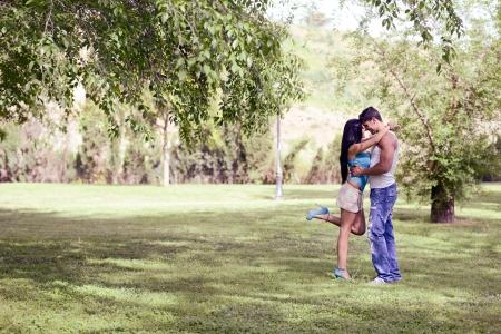 novios besandose: Atractivo joven pareja besándose en un parque