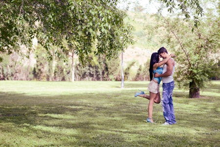 young couple kiss: Attractive young couple kissing in a beautiful park