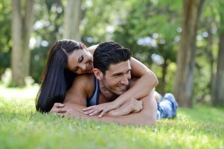 jovenes enamorados: Feliz pareja sonriente que pone en hierba verde en un hermoso parque