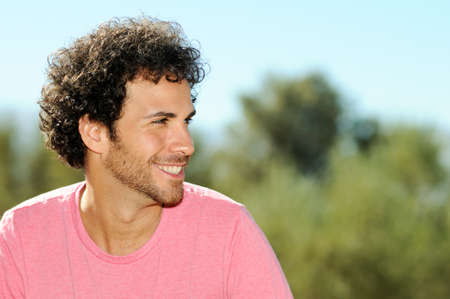 Portrait of handsome man with curly hairstyle smiling, outdoors