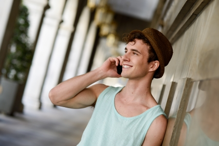 Portrait of an attractive young man wearing hat talking on the mobile phone Banco de Imagens