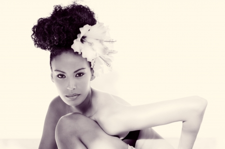 Portrait of a young black woman, model of fashion, with big flowers in her hair  Stock Photo