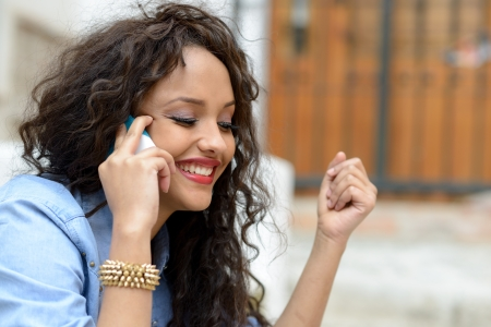 calling on phone: Portrait of beautiful mixed woman in urban background on the phone