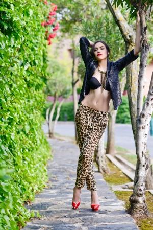 tacones rojos: Retrato de mujer joven y bella, modelo de moda, con pantalones de leopardo, chaqueta y zapatos de tacón alto de color rojo en fondo urbano