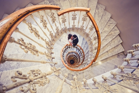 Just married couple together in a spiral staircase