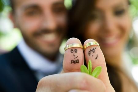 bruilofts -: trouwringen op hun vingers beschilderd met de bruid en bruidegom, grappige kleine mensen