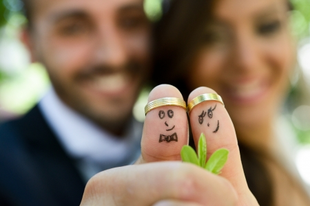 wedding rings on their fingers painted with the bride and groom, funny little people  photo