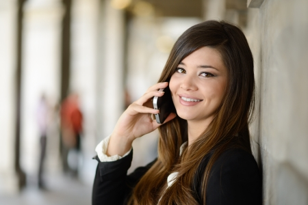 Portrait of japanese business woman in urban background on the phone photo