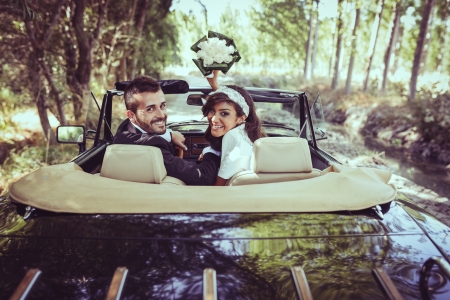 Just married couple together in an old car photo
