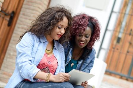 riendo: Retrato de dos hermosas chicas con tablet PC en backgrund urbana, las mujeres negras y mixtas. Amigos que hablan