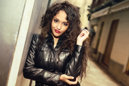 african women: Portrait of attractive black woman in urban background wearing leather jacket