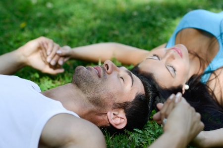 Happy smiling couple laying on green grass in a beautiful park photo