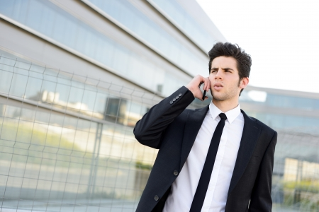 Portrait of an attractive young businessman on the phone in an office building photo
