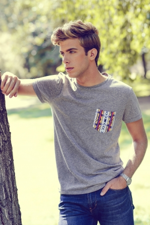 Portrait of a young handsome man, model of fashion, with modern hairstyle in urban background. Blonde hair photo