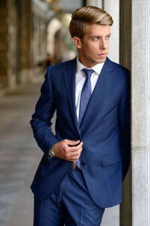 Portrait of an attractive young businessman in urban background wearing blue suit a necktie  Blonde hair photo