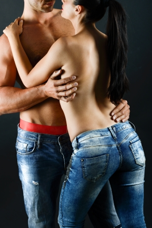 Sexy young couple with blue jeans standing together, studio shot photo