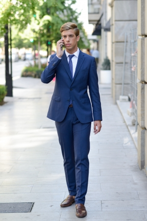 Portrait of an attractive young businessman on the phone in urban background, wearing blue suit and tie. Blonde hair photo
