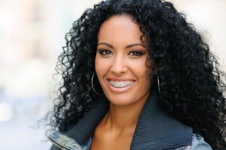 zrozumiały: Portret młodej kobiety czarnym uśmiecha z szelkami