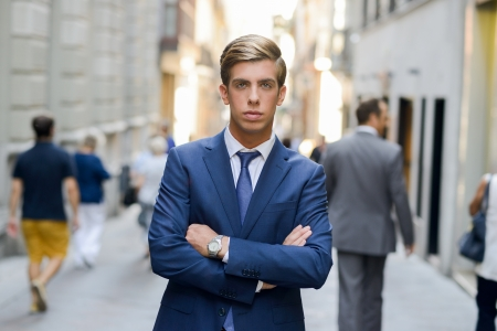 Portrait of an attractive young businessman in urban background wearing blue suit a necktie. Blonde hair photo