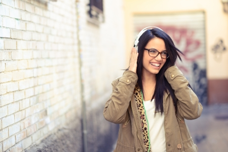 Portrait of young attractive girl in urban background hearing music with headphones