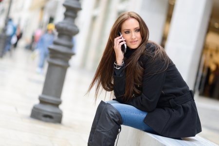 Portrait of beautiful young woman in urban background talking on phone  Stock Photo - 24896556