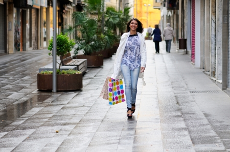Portrait of a beautiful woman with shopping bags walking along a commercial street photo