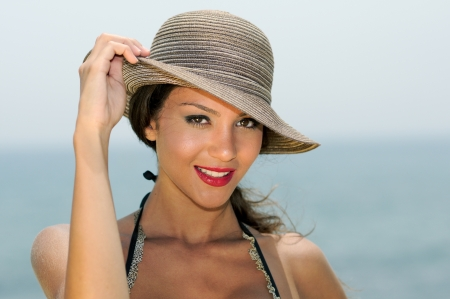 Close up portrait of an beautiful woman smiling with a sun hat on a tropical beach  photo