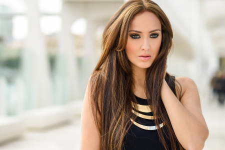 Portrait of a young woman, wearing casual clothes, with long hair in urban background  photo