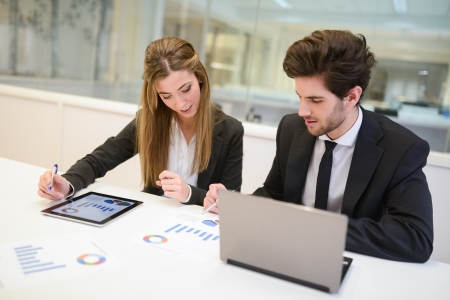 Portrait of business man and woman working around table in modern office  photo