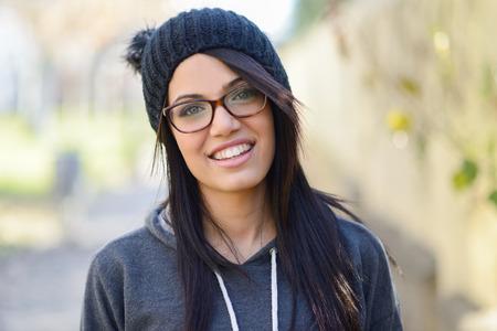 도시 배경에 녹색 눈을 가진 갈색 머리 젊은 여자의 초상화를 입고 녹색 캐주얼 의류, 안경, 모자, 스톡 콘텐츠